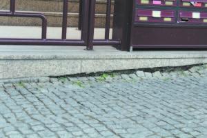 O abatimento do passeio é visível junto a entrada do edifício
